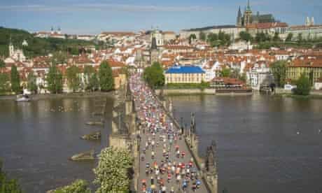 Runners in the Prague marathon cross the Charles bridge