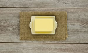 A creamy block of yellow butter on a cream ceramic butter dish on burlap. On weathered boards.
