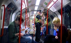 Police officers patrol the London underground