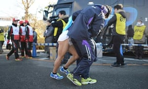 An exhausted runner is led away by his teammates at the Hakone ekiden