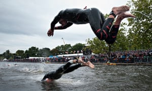 Triathletes dive into the Serpentine in Hyde Park, London.