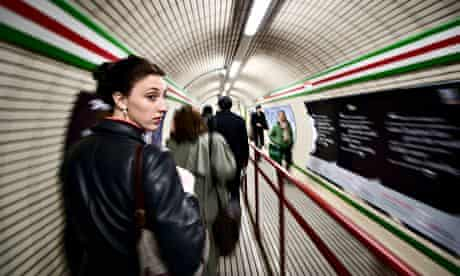 A woman looks back while walking down a hallway on the tube