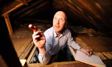 surveyor shining torch into loft