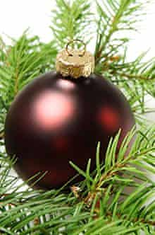 A red christmas ornament with christmas tree