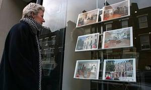 woman looking in estate agents window
