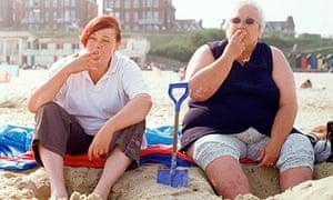 Two women smoking on the beach