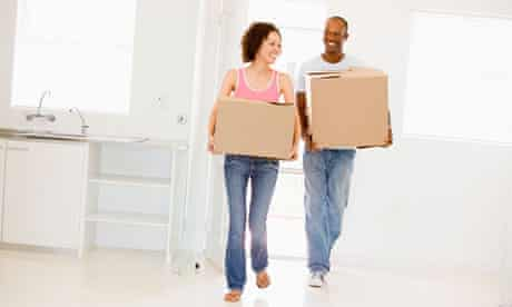 Couple with boxes moving into new home