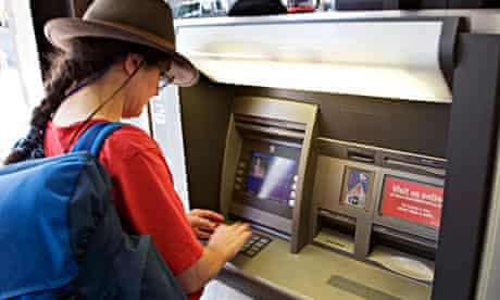 Woman tourist using an ATM machine Seattle USA