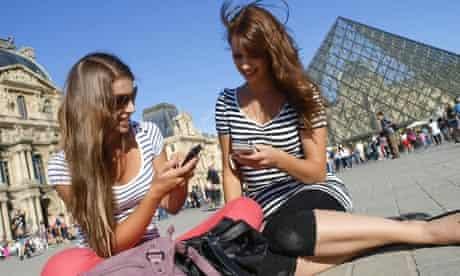 women on phone next to Louvre, Paris