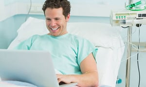 Happy male patient typing on a laptop