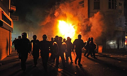 Riot police stand in front of a burning building