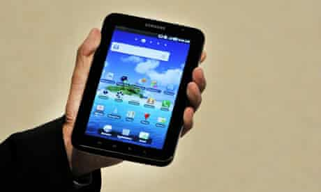 A hand holds up a Samsung Galaxy tablet