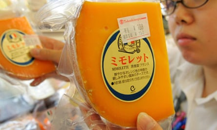 Salesperson replenishes stocks of French cheese