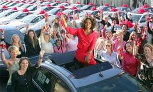 Talk show host Oprah Winfrey sits atop a Pontiac G6 surrounded by some of the 276 audience members who each received one of the cars to celebrate the start of her 19th season in 2004. Photograph: Bob Davis/AP