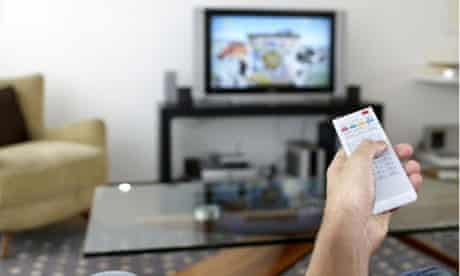 A man watching TV using a remote control