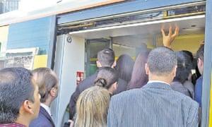 Commuters board a train at East Croydon