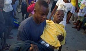 A man carries a child with cholera symptoms in Port-au-Prince, Haiti