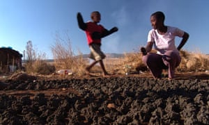 Children play with patties made of coal dust in a shantytown near Newcastle, South Africa