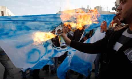 Palestinians burn a mock Israeli national flag