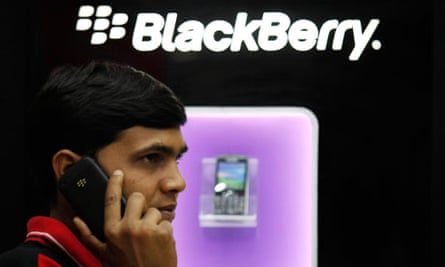 A man speaks on a BlackBerry mobile phone inside a shop in Kolkata, India