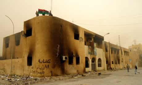 Libyan protesters hold a flag on top of a building.
