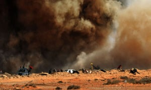 Libyan rebel fighters run for cover as a