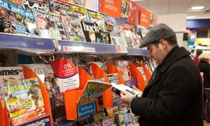 A man looking at magazines in WH Smiths, Cambridge UK