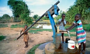 Children pumping water from village well in Zimbabwe