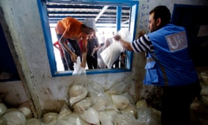 Palestinians crowd a window for food aid at a United Nations distribution centre in Gaza City