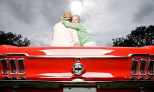 A senior couple in a sports car