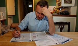 man filling in tax form