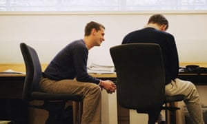 Two workers talk in an office