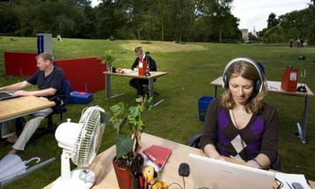 Office workers sit at desks outside