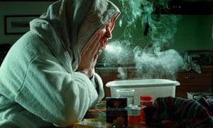 A man suffering with flu holds his head over a bowl of steaming water