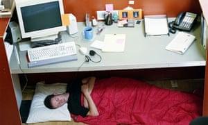 A man asleep under his desk at work