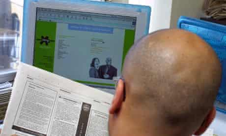 A jobseeker looking at an internet jobs website and a newspaper
