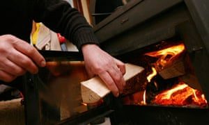 A man loads a wood-burning stove