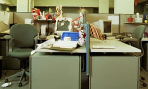 An untidy desk in an office next to a tidy one