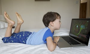 A child lying down playing games on a laptop
