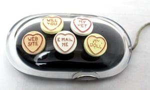 Love heart sweets on a computer mouse.