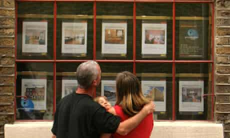 A family looking in an estate agent's window