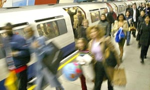 Commuters leave a London Underground train at Green Park Underground station in London