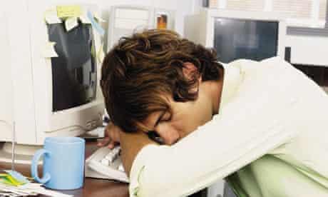 Young Man asleep at work sleeping on computer at desk