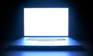 A laptop computer illuminated in the dark