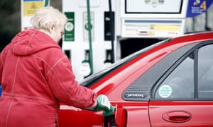 An older woman puts unleaded petrol in her car