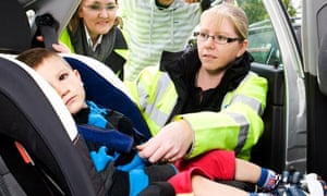 A child seat safety officer helps fit a car seat