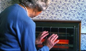 An elderly woman warms her hands on an electric heater