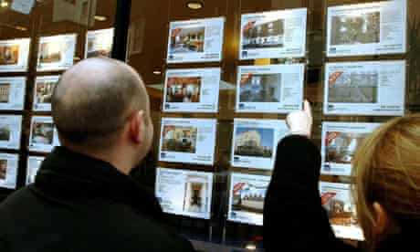 A a couple studying property for sale in an estate agents.