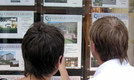 A young couple look in an estate agent's window