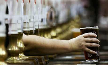 A pint of beer is served through rows of beer pumps